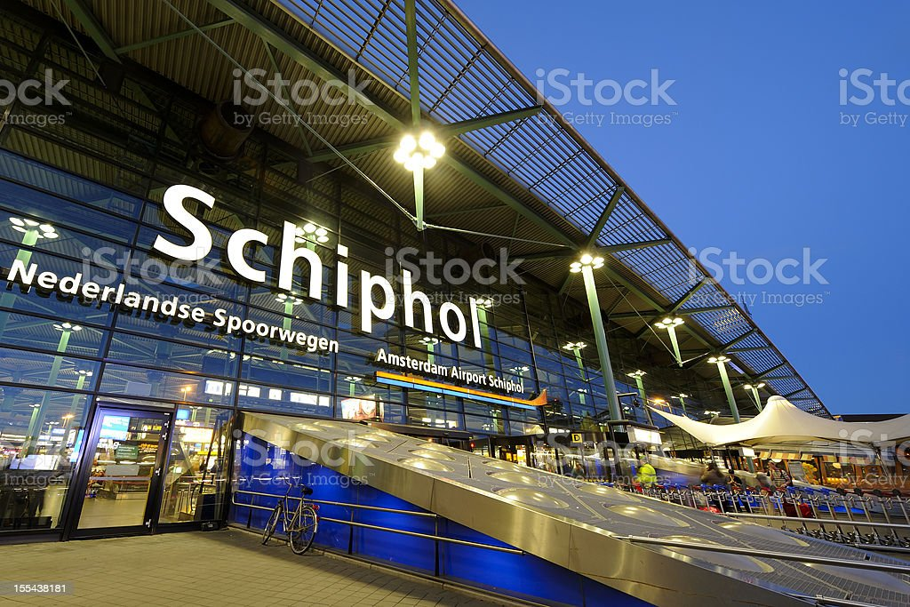 Illuminated entrance of Amsterdam Airport Schiphol at night stock photo