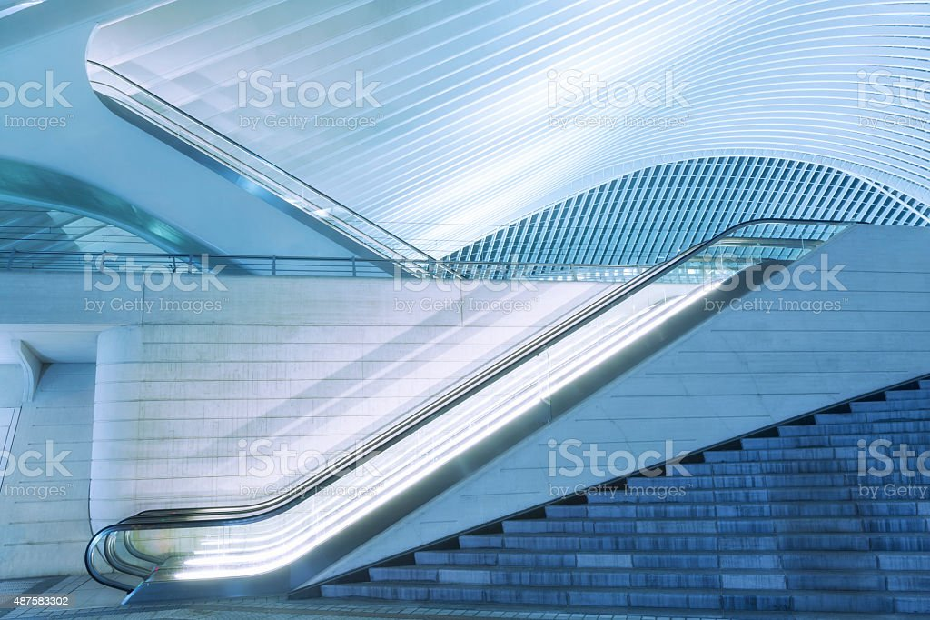 Illuminated Escalator Outside Futuristic Train Station Illuminated at Night stock photo
