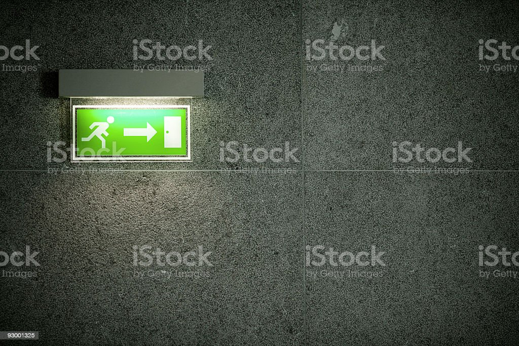 Illuminated green exit sign on dark large stone tile wall stock photo