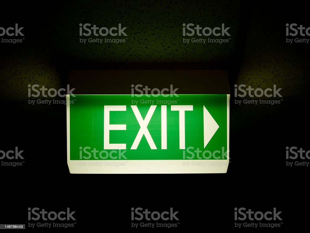 Illuminated green exit sign with an arrow pointing right stock photo