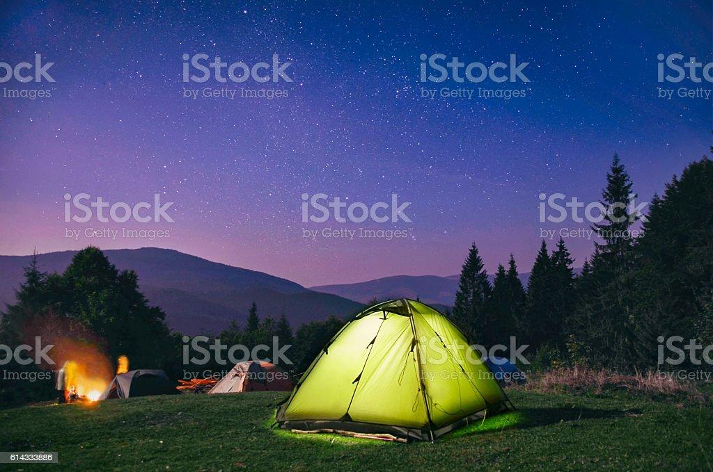 Illuminated  green  tent under stars at night  forest stock photo