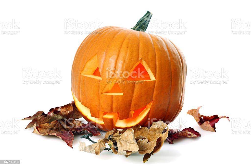 Illuminated Halloween Pumpkin on Autumn Leaves royalty-free stock photo