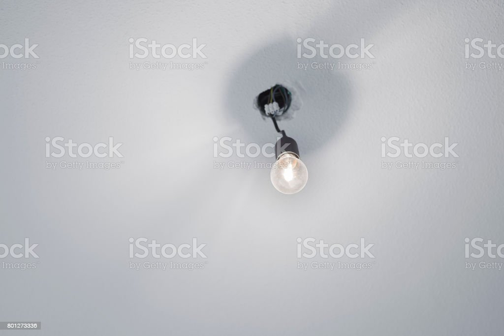 Illuminated halogen incandescent light bulb in a black plastic lamp holder socket with power cables protruding from the ceiling stock photo