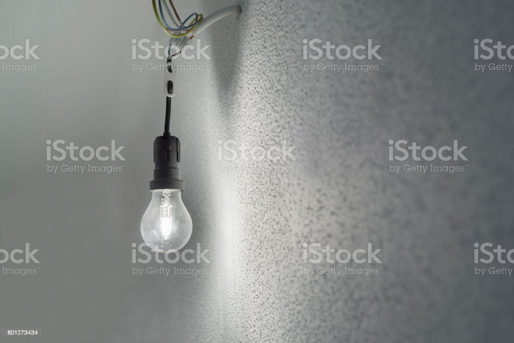 Illuminated halogen incandescent light bulb in a black plastic lamp holder socket with power cables protruding from a wall with white rough plaster stock photo