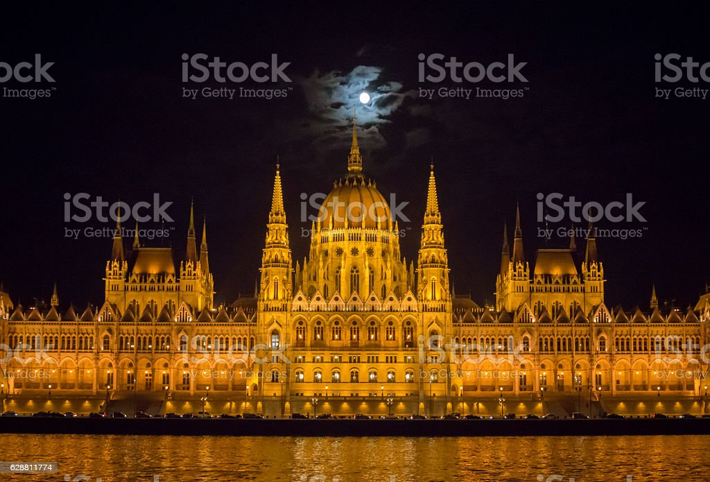 illuminated Hungarian Parliament Building in Budapest at Danube by night stock photo