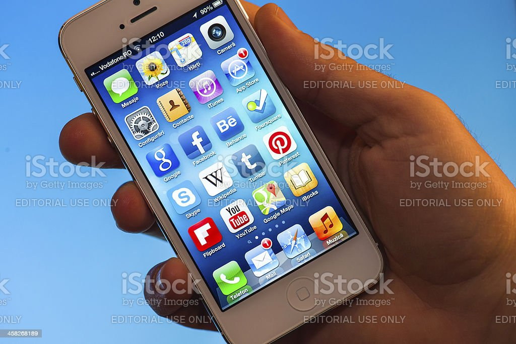 Illuminated iPhone 5 Apps hold in a hand stock photo