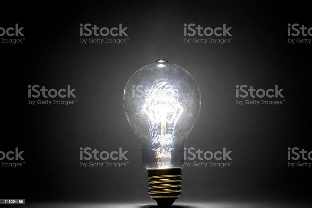 illuminated light bulb on dark background stock photo
