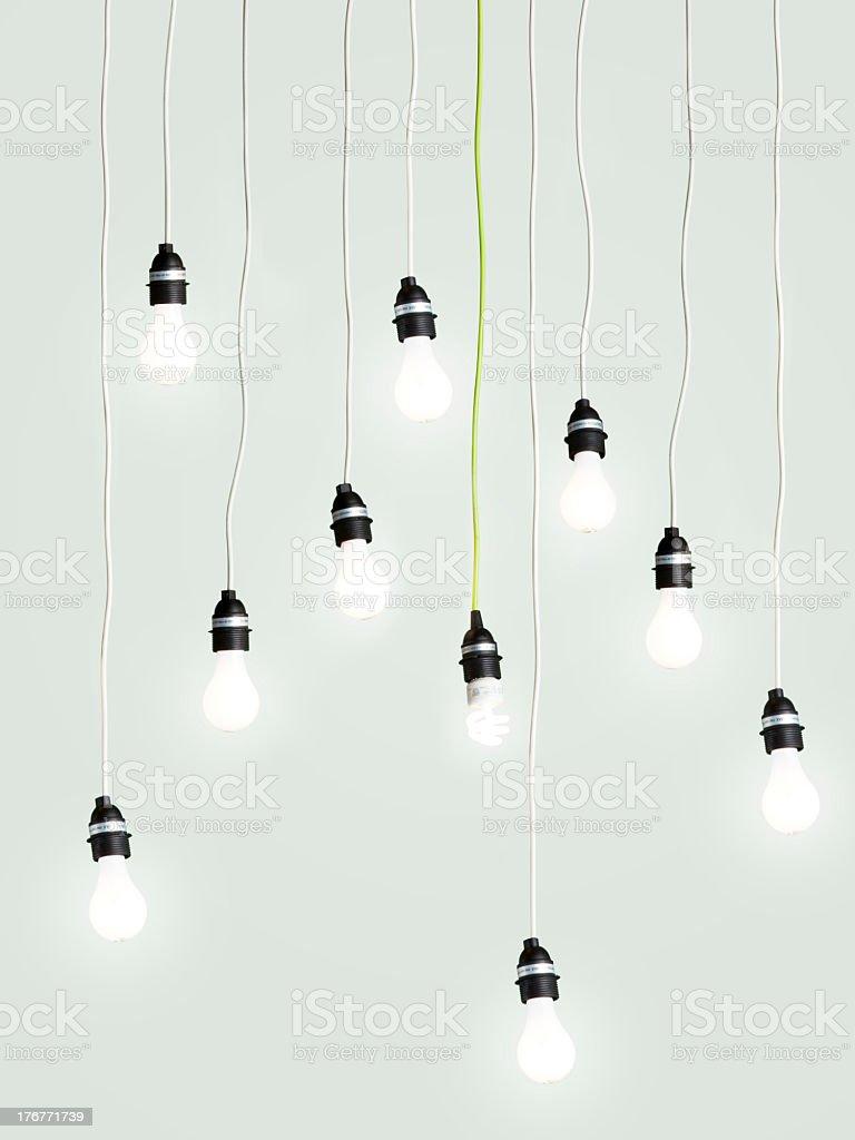 Illuminated light bulbs dangling on green background royalty-free stock photo