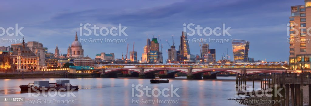 Illuminated London, panoramic view over Thames river from Waterloo bridge in the evening. This image is toned. stock photo