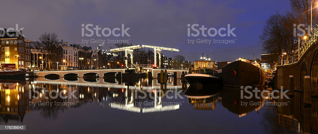 Illuminated Magere Bridge in Amsterdam over reflective water royalty-free stock photo