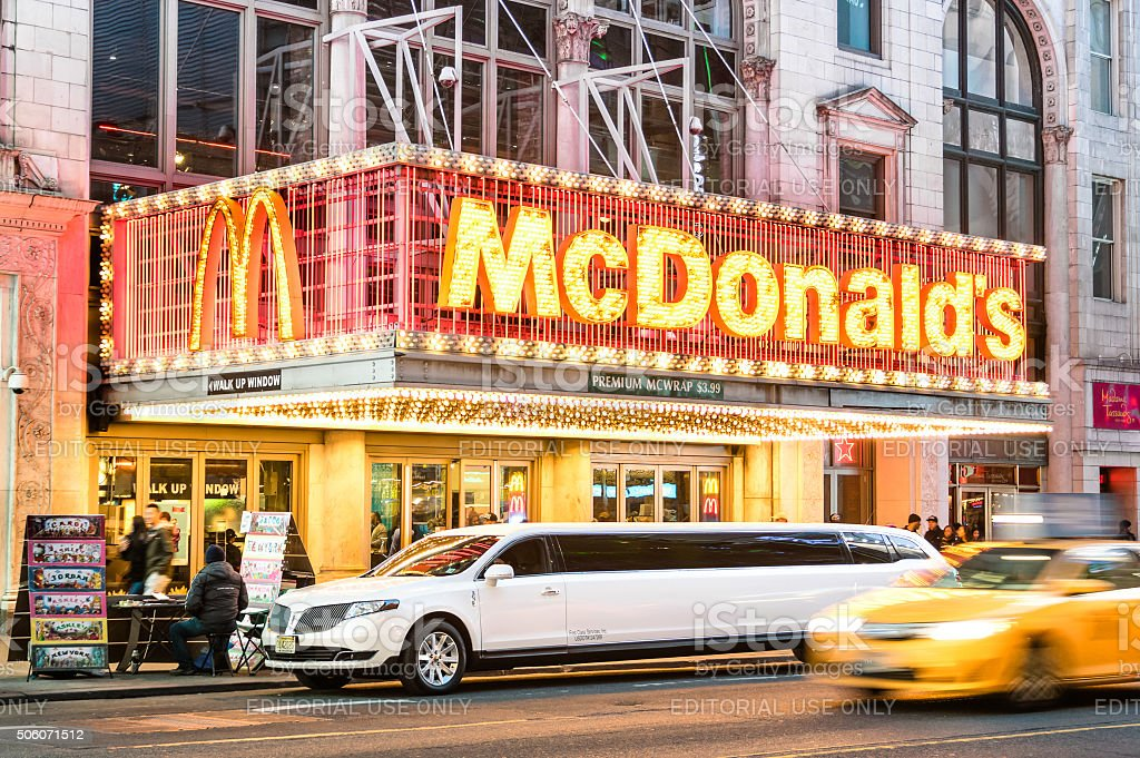 Illuminated neon sign of burger chain Mc Donalds with limousine stock photo