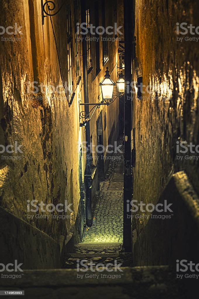 Illuminated old alley in Stockholm by night royalty-free stock photo