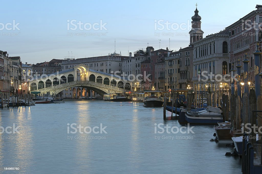 Illuminated Rialto bridge at dusk in Venice, Italy royalty-free stock photo