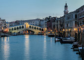 Illuminated Rialto bridge at dusk in Venice, Italy