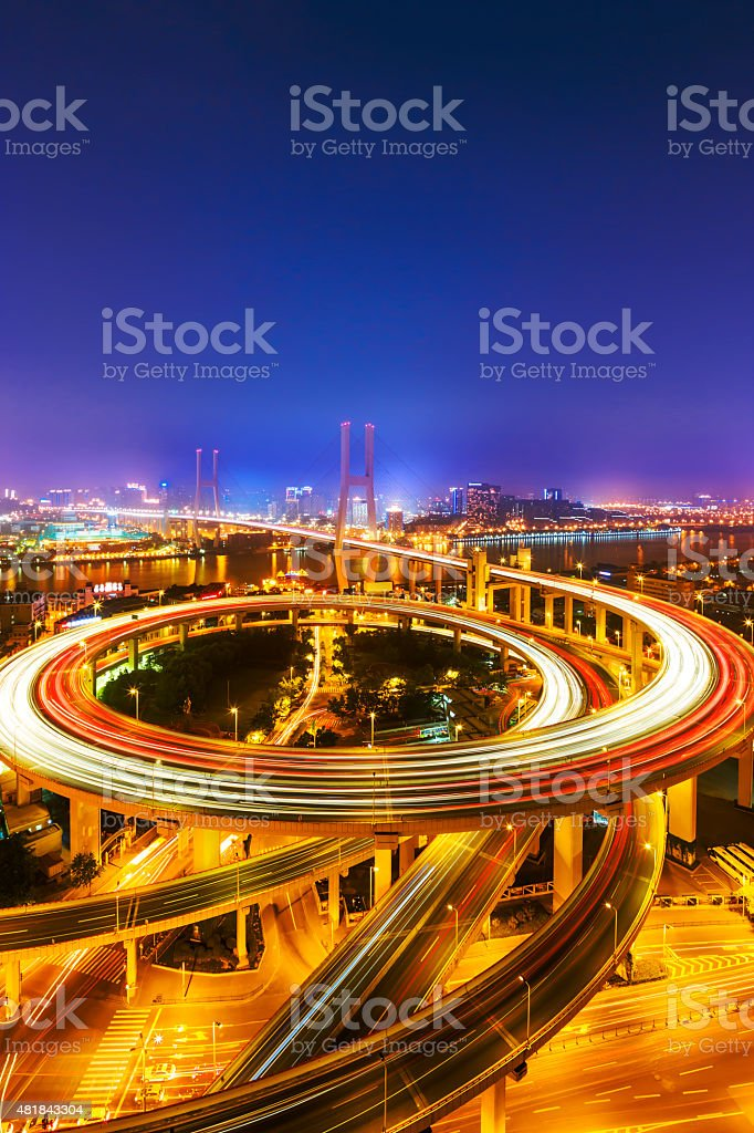 illuminated road intersection and traffic trails stock photo