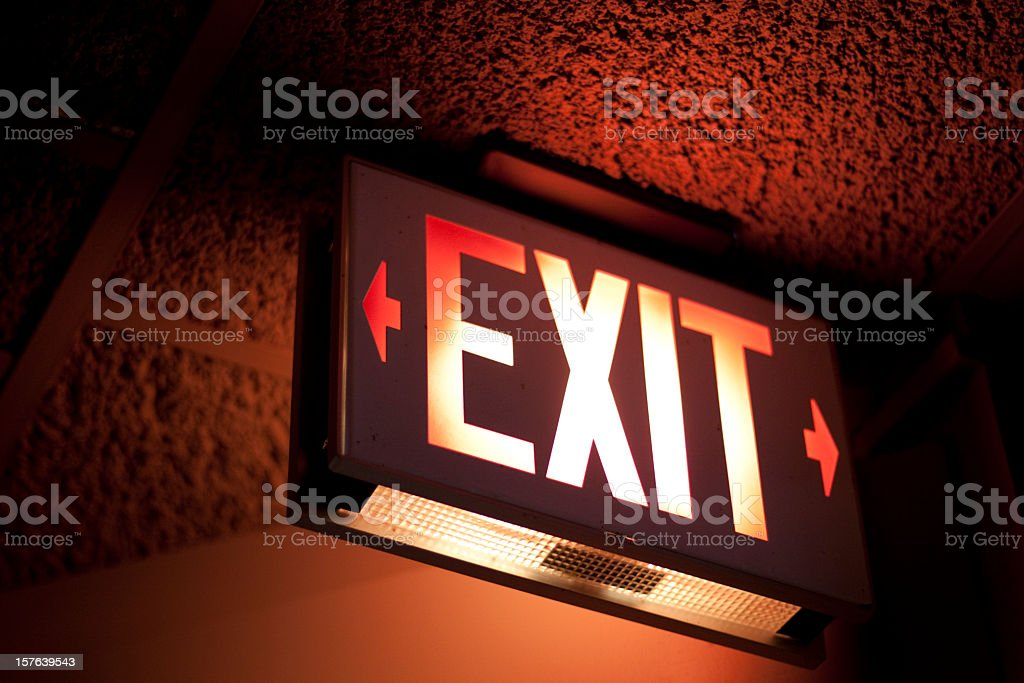 Illuminated sign with word EXIT and arrows under red light stock photo