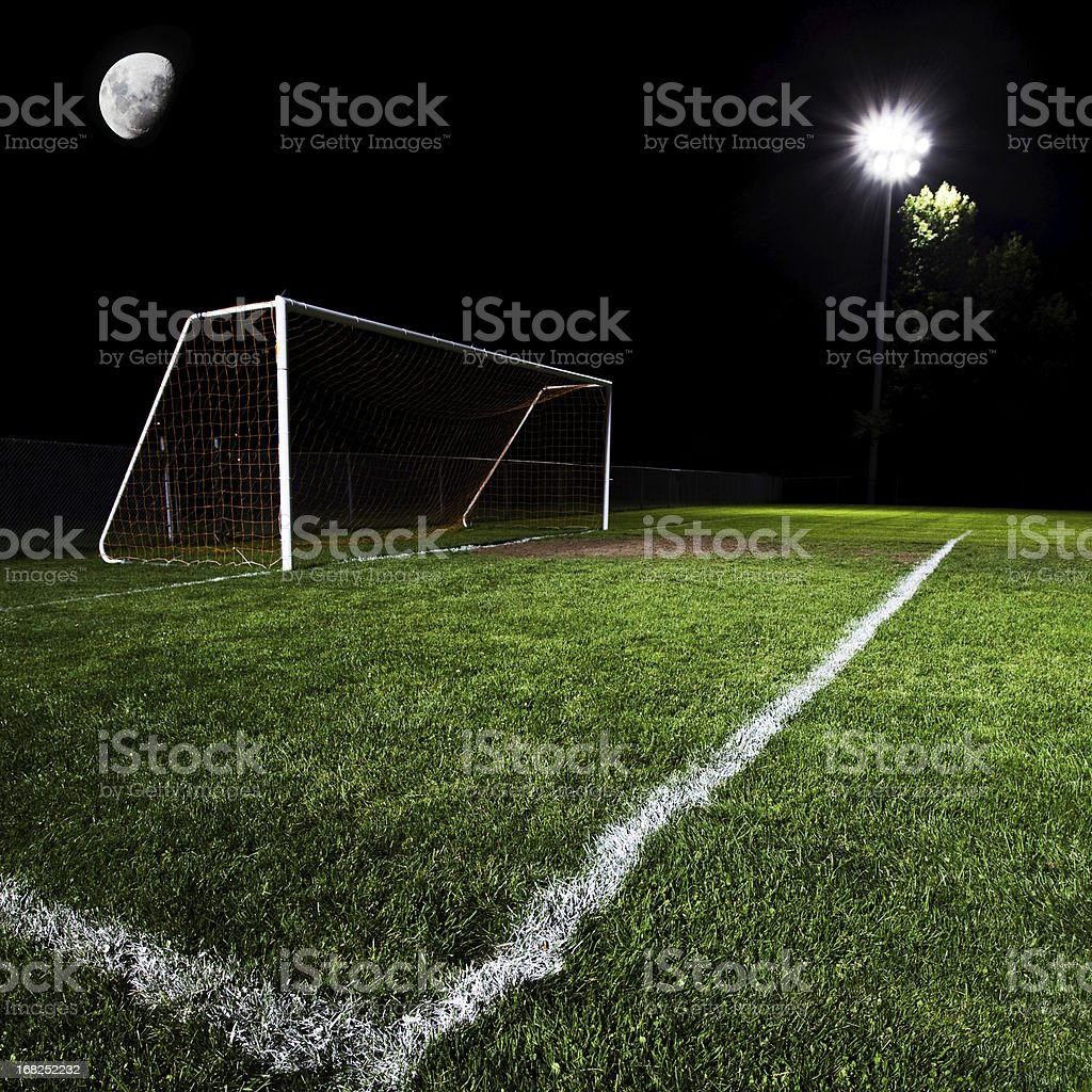 Illuminated soccer goal and field at night royalty-free stock photo