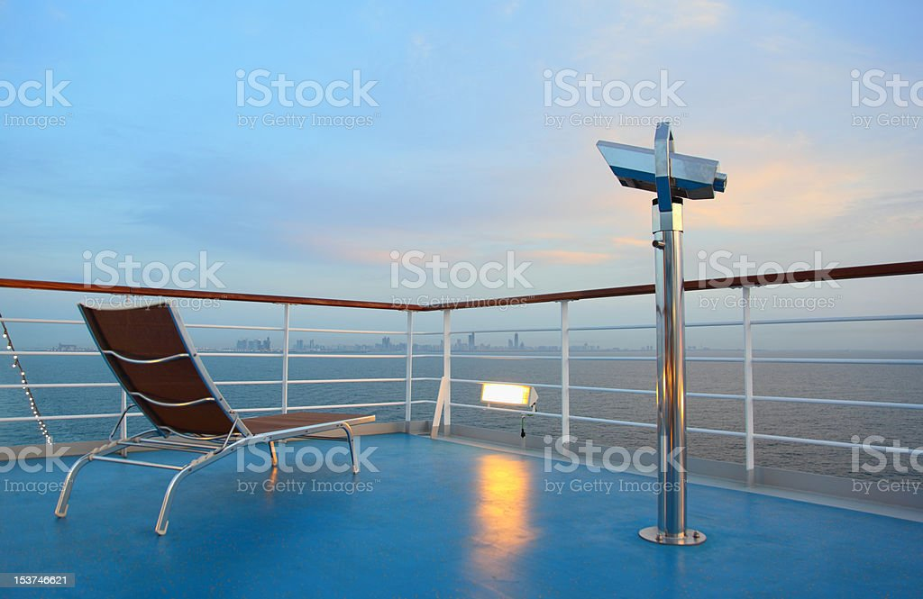 Illuminated solitary deck-chair and binocular on ship royalty-free stock photo