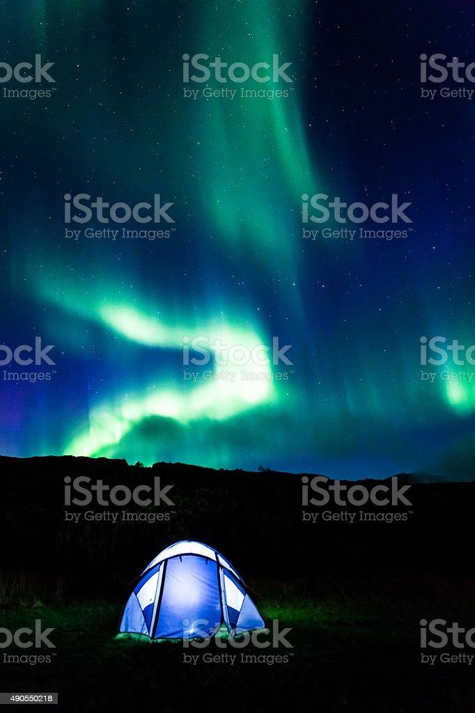 Illuminated tent and aurora in Iceland stock photo