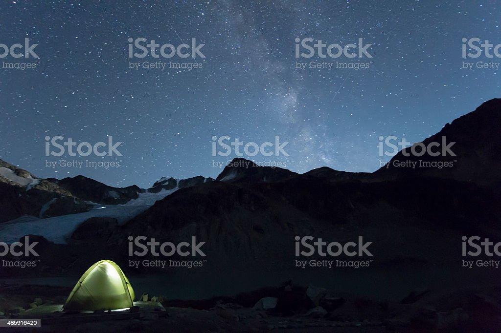 Illuminated Tent in mountains  under the Milky Way Galaxy stock photo