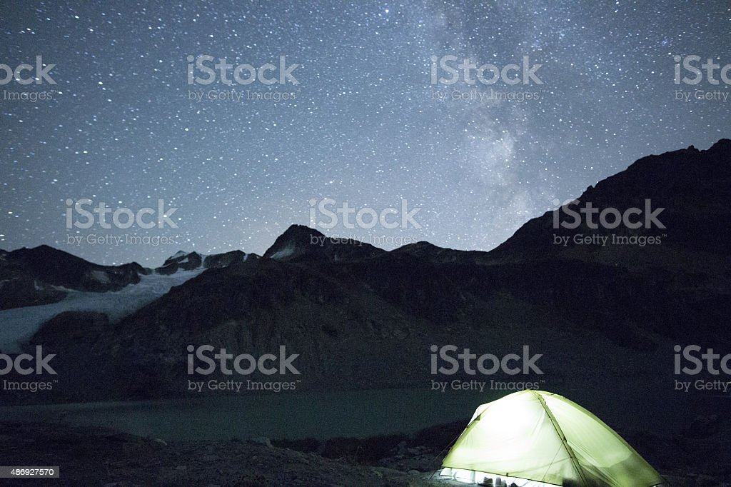 Illuminated Tent under star dotted night sky stock photo