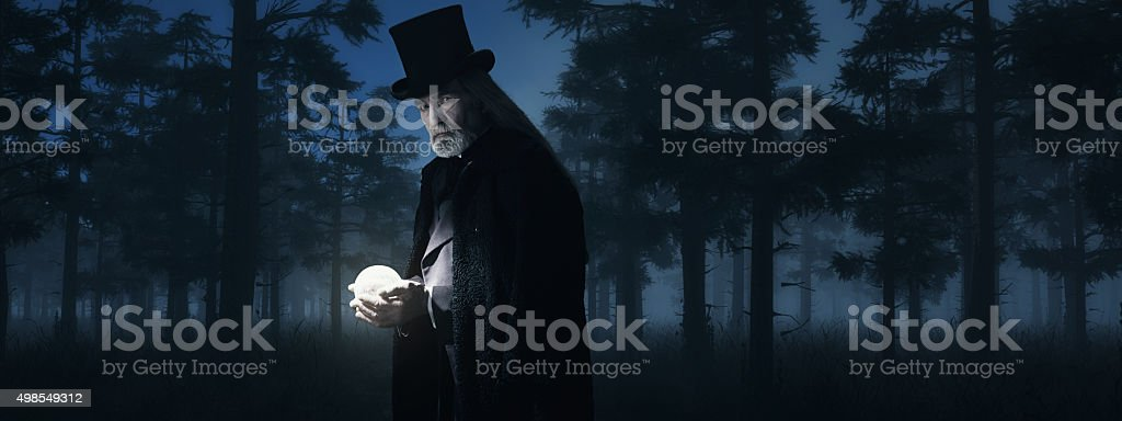 Illusionist Holding Illuminated Sphere in Foggy Winter Forest at Night. stock photo