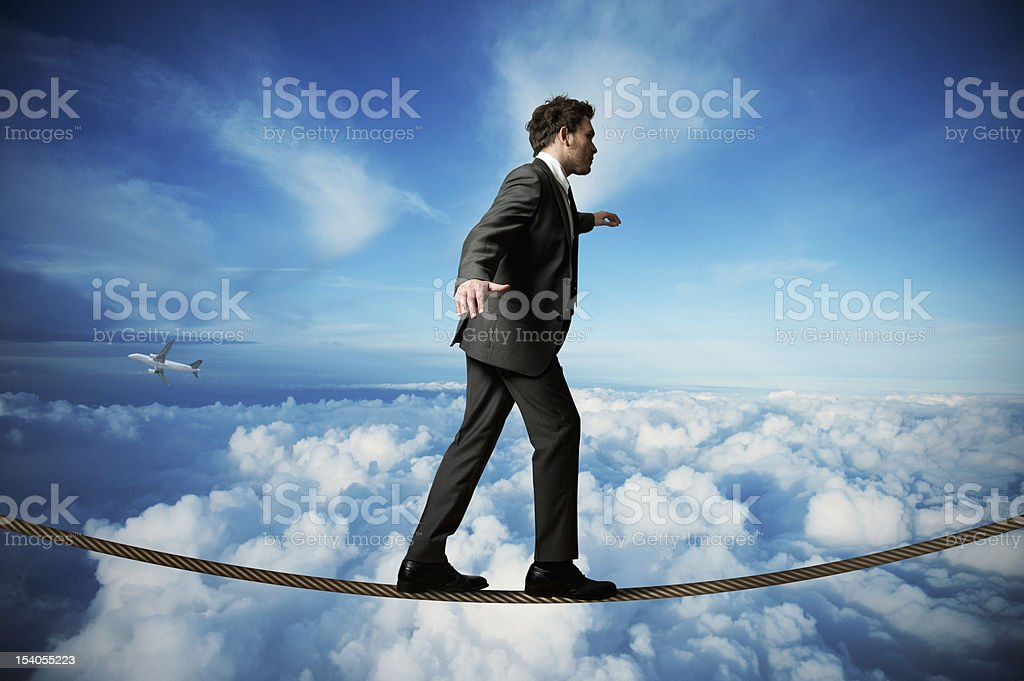 Illustration of businessman balancing on tightrope in sky stock photo