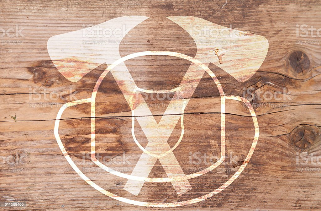 Illustration of white helmet and axes on brown wooden background stock photo