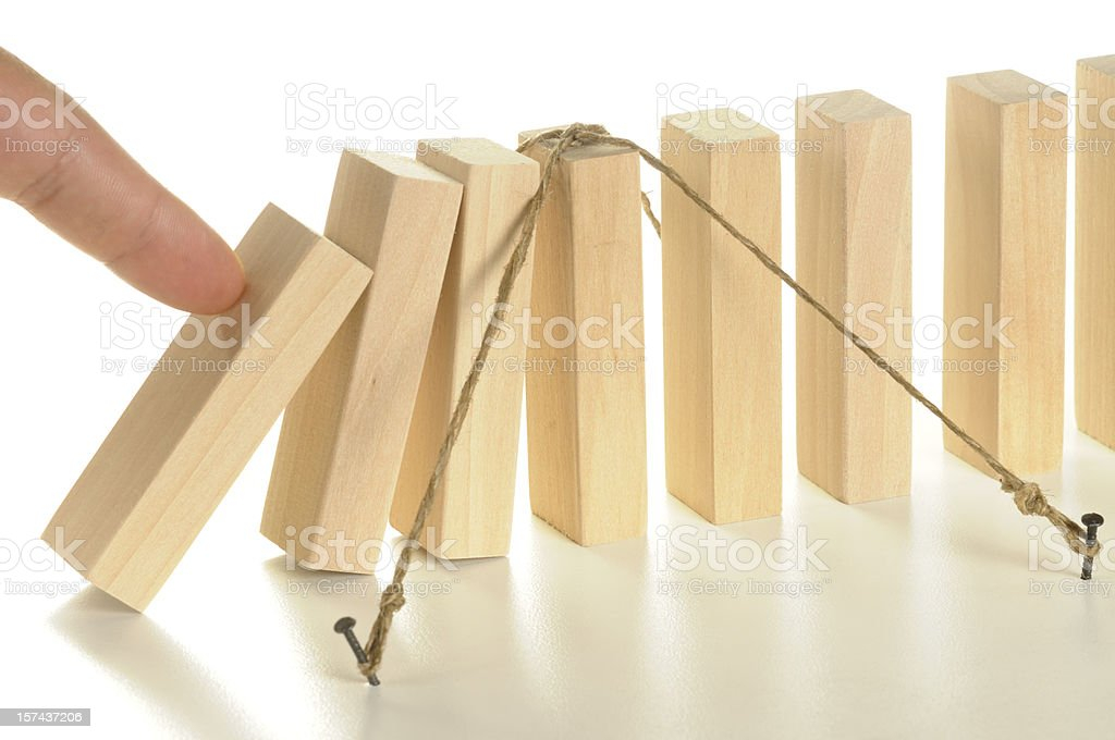 Illustration using tethered wooden dominos for insurance stock photo