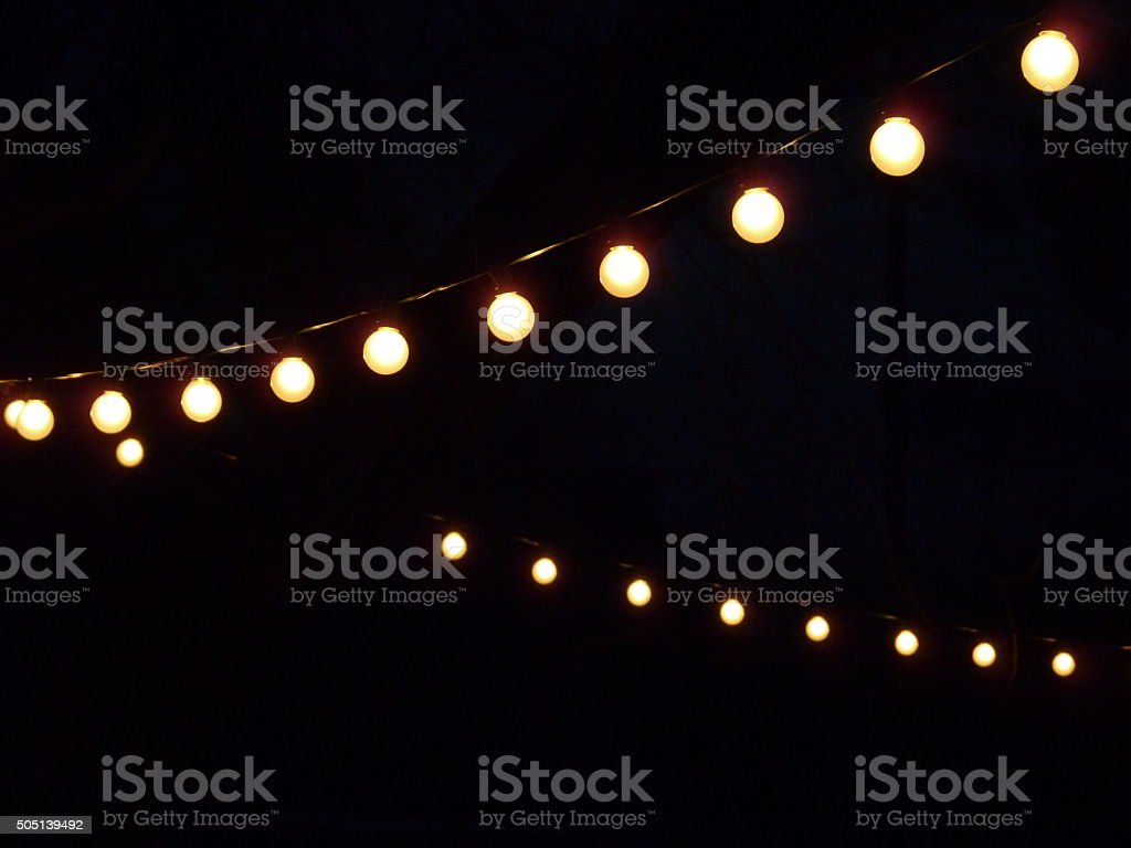 Ilummination from Strings of White Bulb Electric Lights at Night stock photo