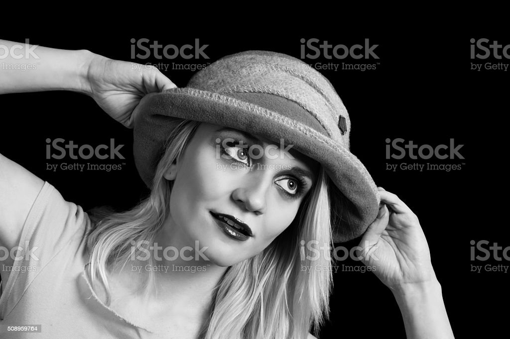 B&W image, blonde woman pulling on winter hat, looking away. stock photo