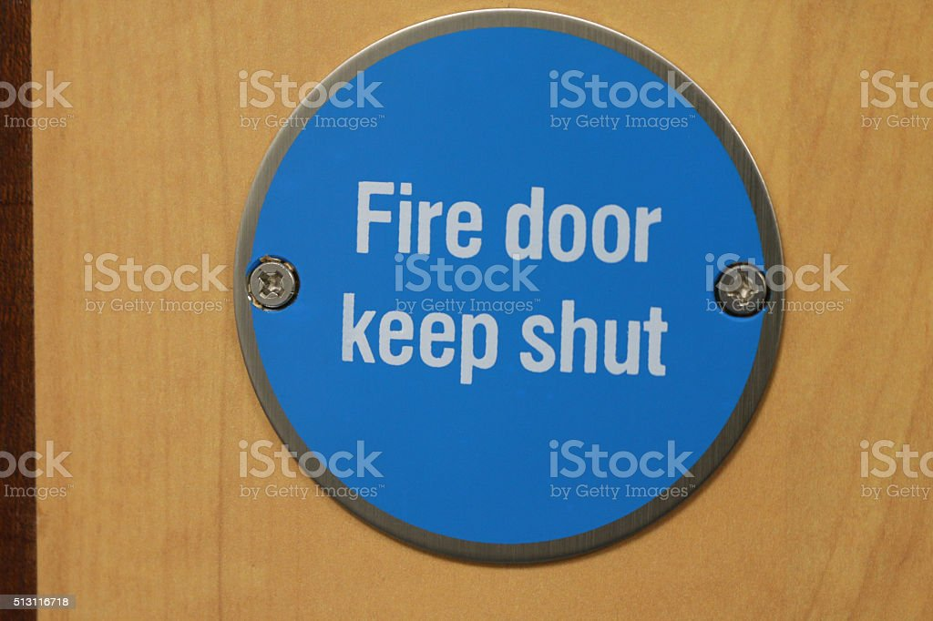 Image close-up of blue-circular advisory sign on emergency fireproof door stock photo