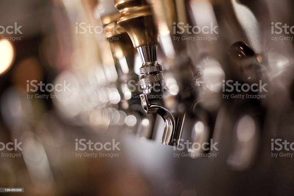 Image focusing on the taps in a brewery stock photo