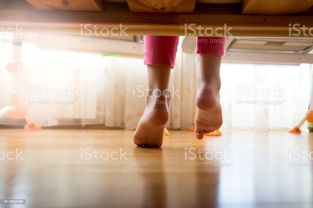 Image from under the bed on girl stepping on floor stock photo