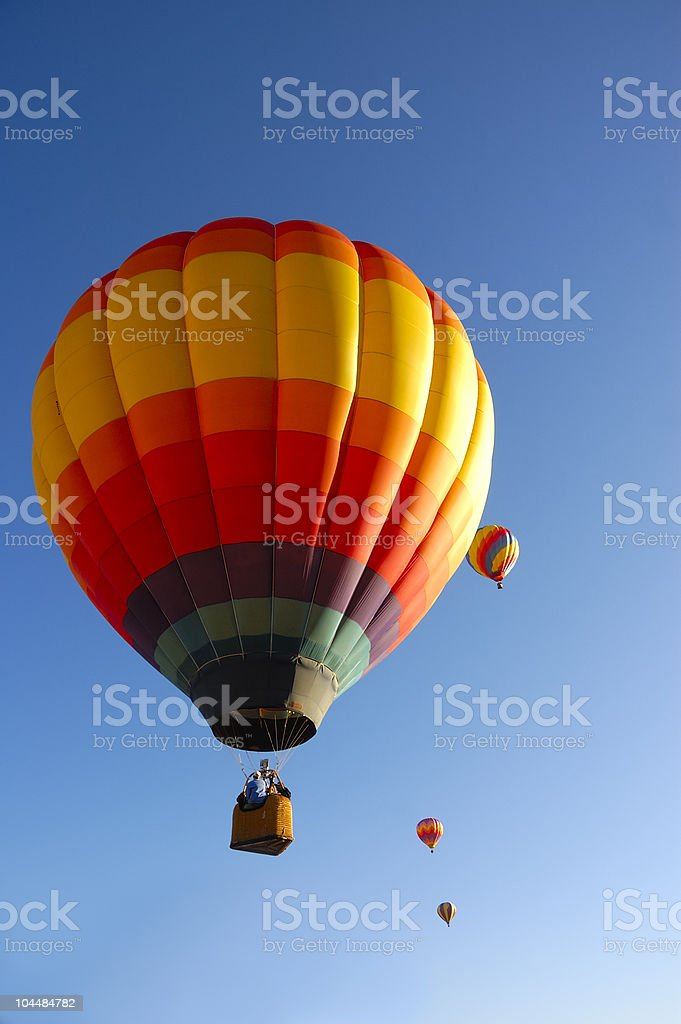 Image of 4 multicolored hot air balloons against a blue sky royalty-free stock photo