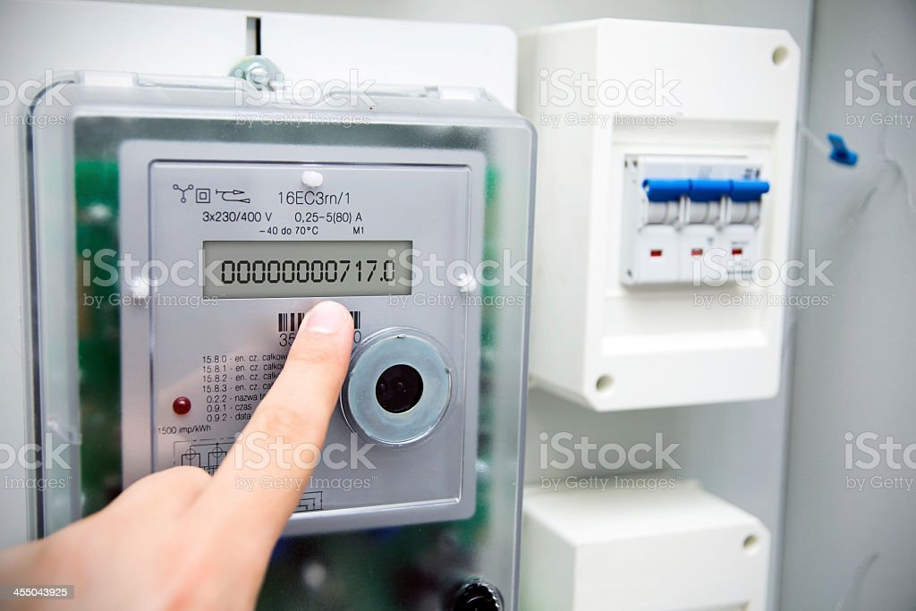 Image of a finger pointing at a modern electric meter  stock photo