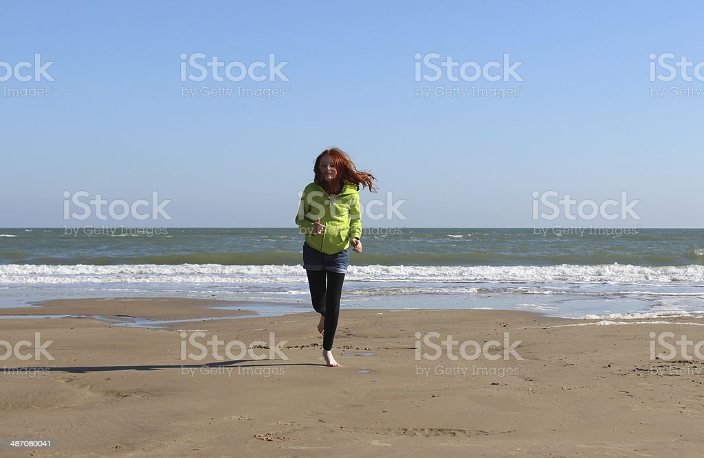 Image of a girl running along the beach in the sun royalty-free stock photo