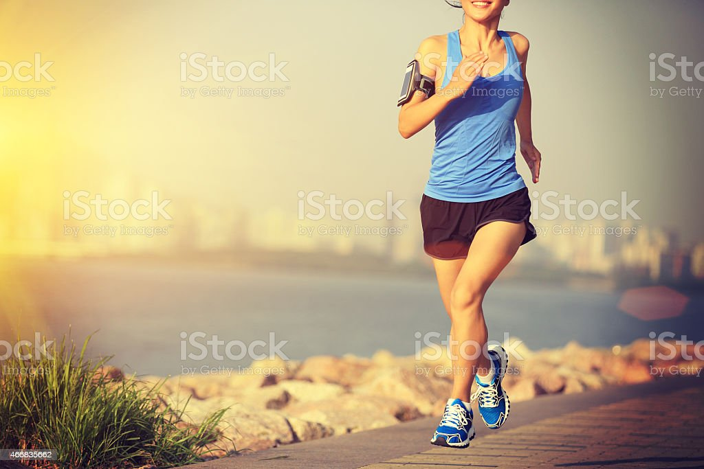 Image of a healthy woman running along the beach stock photo