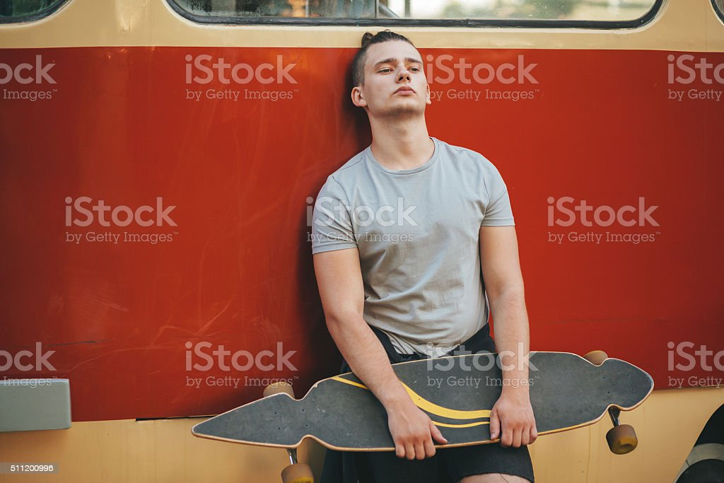 Image of a man with longboard going on road stock photo