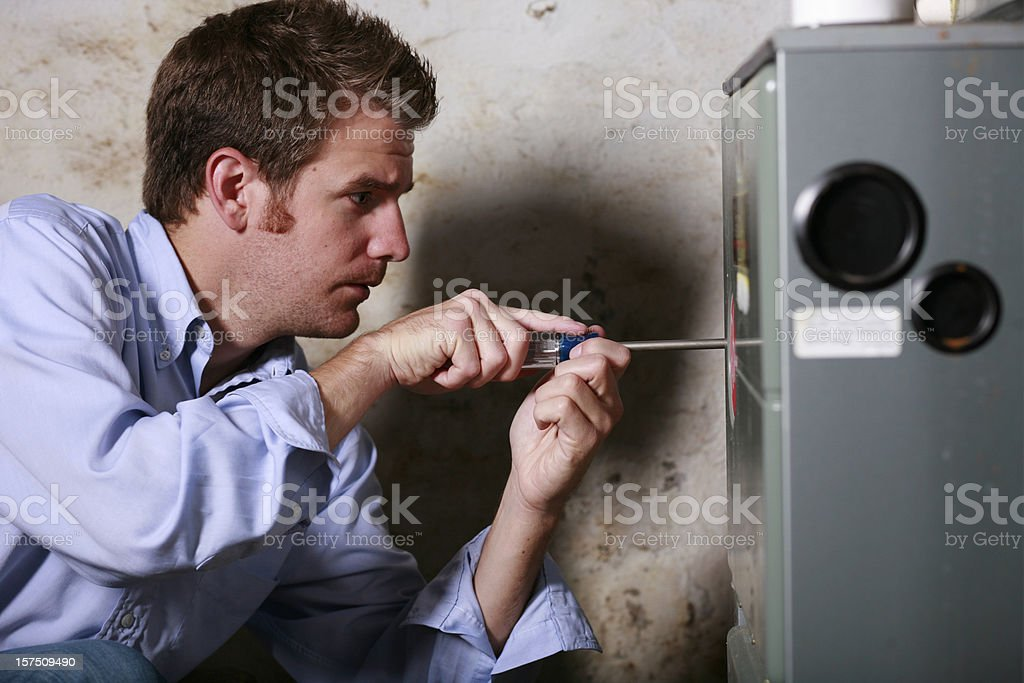 Image of a man working on a furnace with a screwdriver stock photo