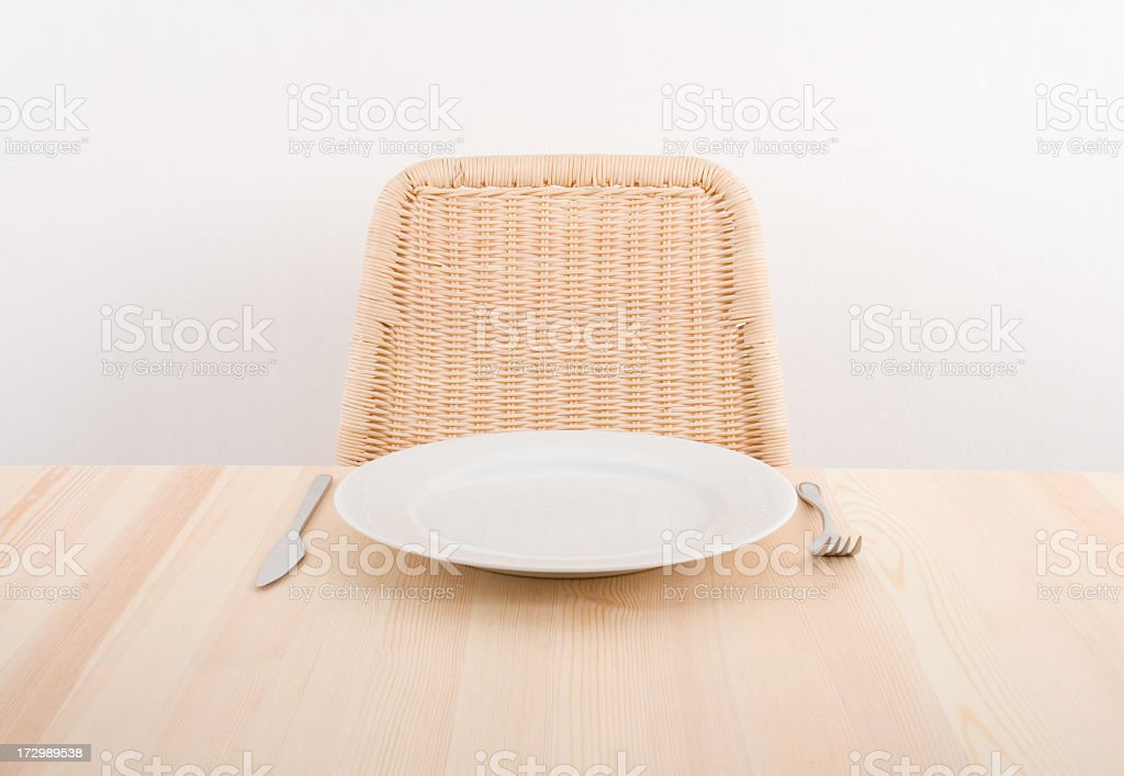 Image of a single plate with an empty seat at a table stock photo
