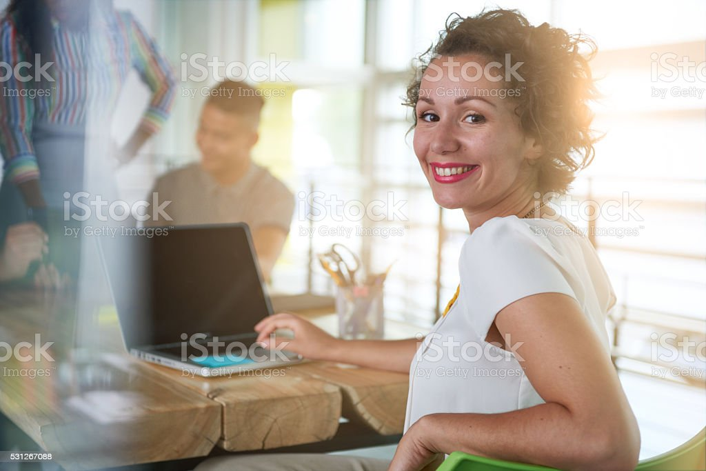 Image of a succesful casual business woman using laptop during stock photo