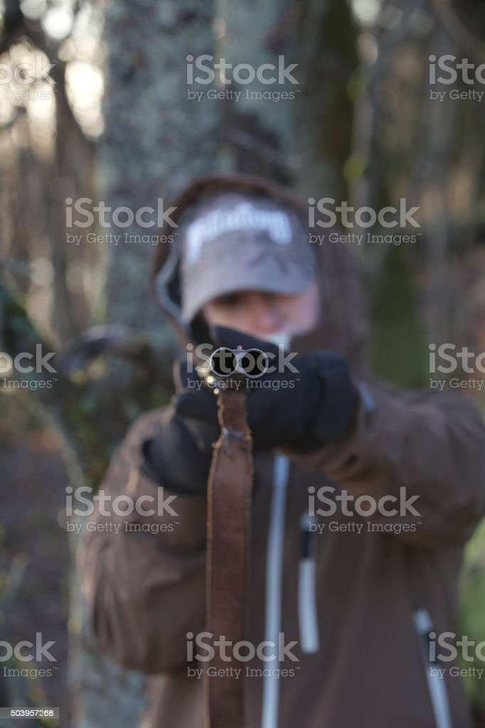 Image of a young person with a shotgun stock photo