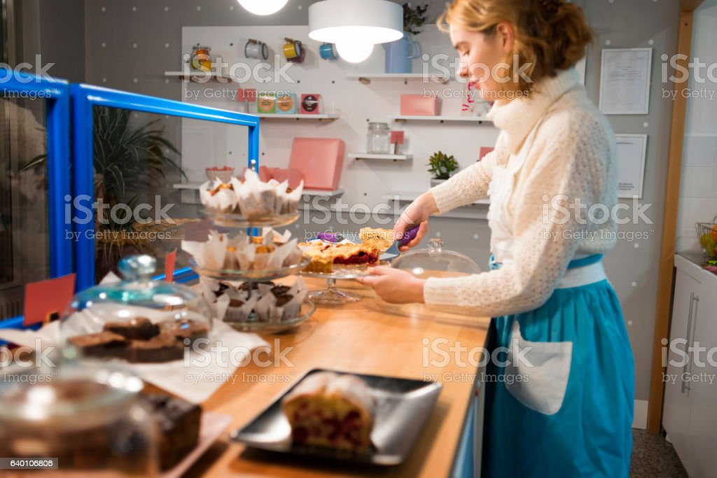 image of a young waitress arranging cakes stock photo