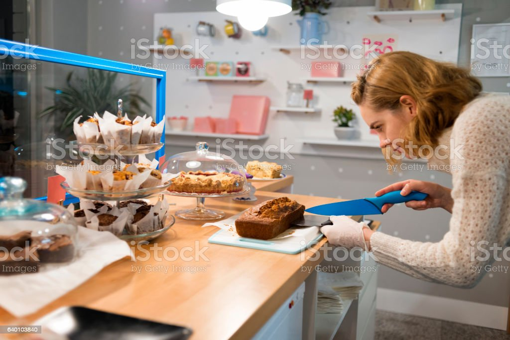 image of a young waitress cutting pastries stock photo