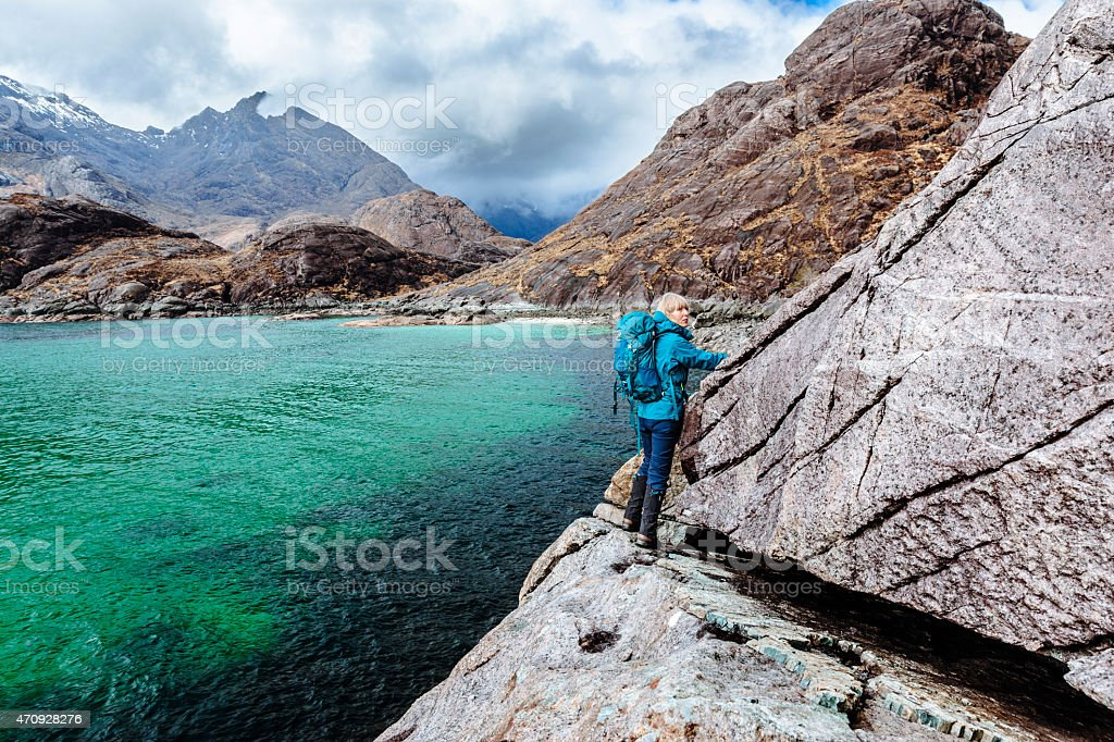 Image of a young woman preparing to scale Bad Step on Skye  stock photo