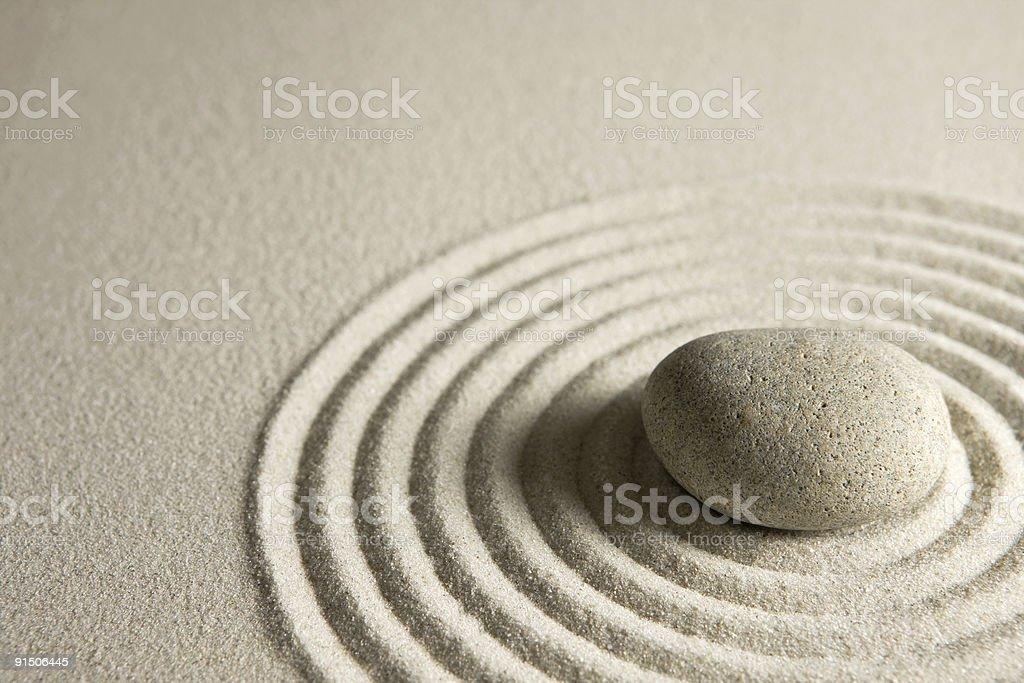 Image of a zen stone in circles of sand stock photo