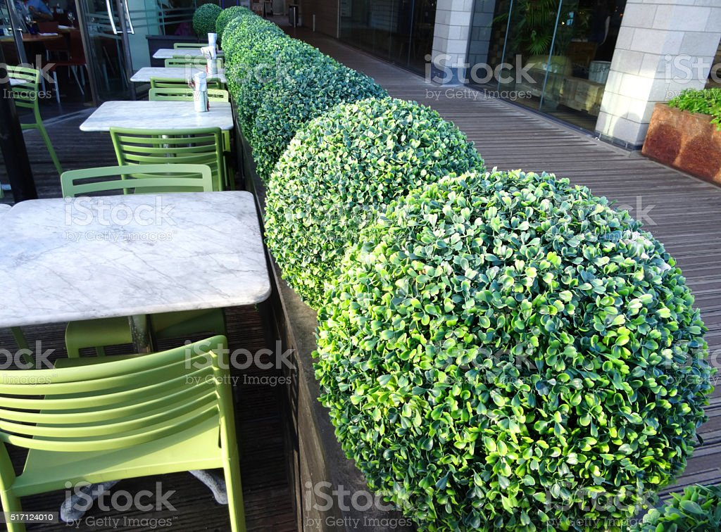 Image of alfresco pavement restaurant tables and chairs, artificial plants stock photo