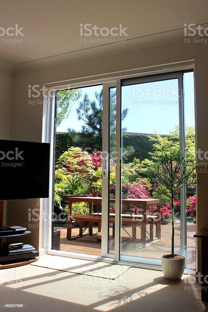 Image of aluminium patio doors overlooking back garden with decking stock photo