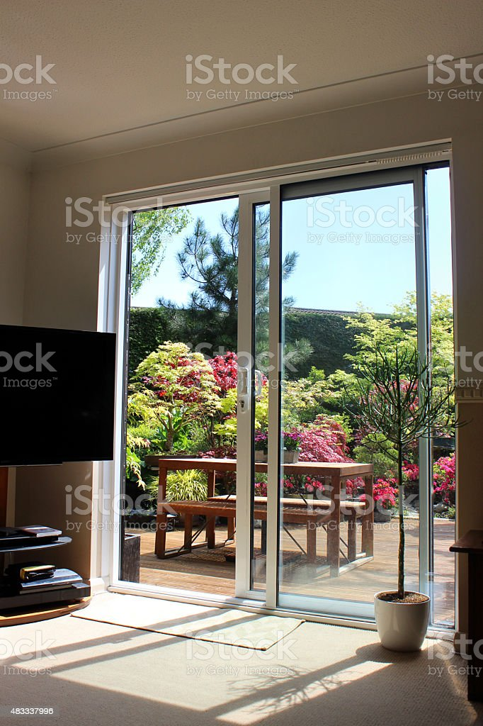 Image of aluminium patio doors overlooking back garden with decking stock photo